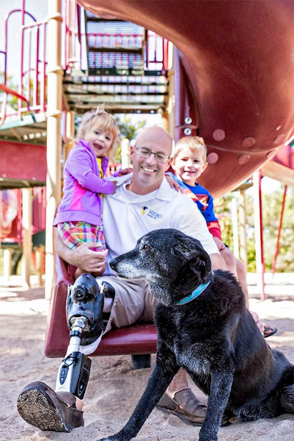 Ben Blecha sitting on slide with son, daughter, and dog